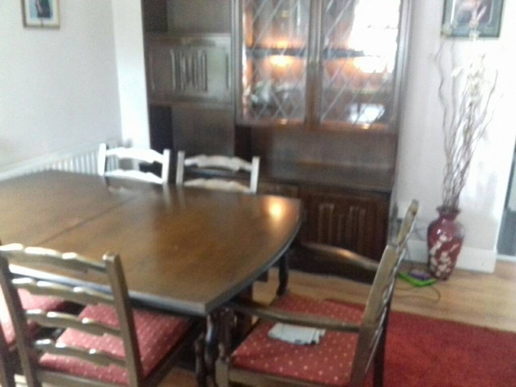 Dark oak dining room table with 6 chairs and matching wall unit
