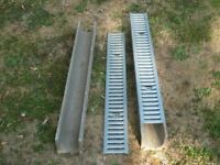 Two unused concrete casing drainage channels with metal grates