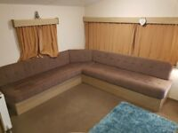 Static caravan corner seating in brown with pull out bed.