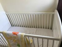 White cot bed with bedding and mattress