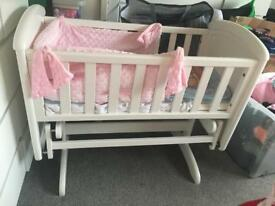 White solid wood swing crib with pink and blue bumper set