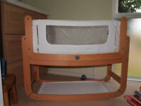 SnuzPod² Bedside Crib and x2 Mattress with green sheep mattress protector - natural wood