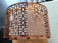 A pair of metal copper colour fret ceiling lampshades.