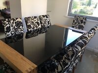 Distinctive black glass dining table with 8 chairs