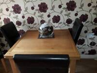 Solid oak extendable dinning table and 4 leather back chairs