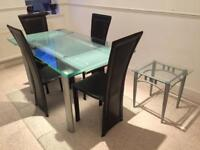 Glass dining table with four black chairs and side table
