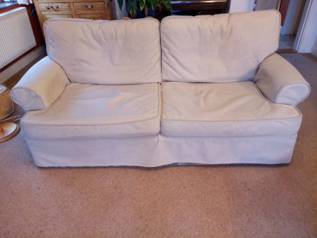 2-3 seater beige upholstered sofa with loose covers