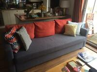 Three seater sofa-bed FRIHETEN with orange back cushions