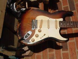 Stratocaster style guitar in distressed sunburst finish
