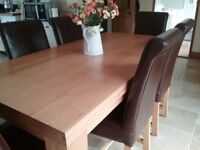 Solid oak dining table and six braced leather chairs