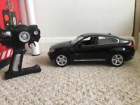 BMW X6 RC car with lights shining on the front and back.