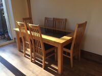 Solid oak dining table with glass and 6 chairs for sale.