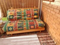 Double Futon with Pine Frame and mainly green coloured cushion