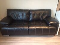Black leather couch which thick white stitching