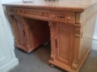 A large pine pedastel desk in good condition with nice detailing