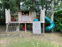 Kids wooden tree house with tunnel slide, swings, rope ladder and more.