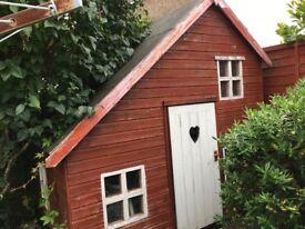 Wooden children's playhouse with upstairs area, cottage door & windows.