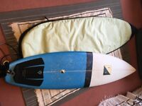 "UA Surfboard 6'4"" x 20 1/2"" x 2 5/8"". Blue shortboard with fins, leg rope and travel bag"
