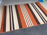 Orange, brown and cream striped rug