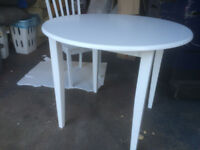 New round white wood table and 3 chairs.