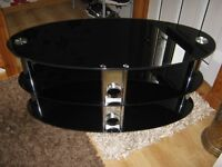 TV Stand, black glass with silver tubing it has three shelves a 40 inch TV would fit on it