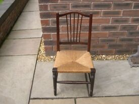 A child's wooden chair with rush seat.