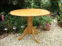 Hardwood circular drop leaf four seater dining table...
