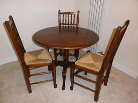 Round solid light oak tilt top table and 3 solid light oak spindleback chairs.