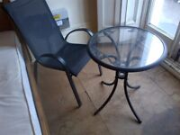 small near new glass top table with easy chair can deliver