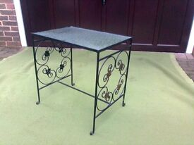Small table suitable for living rooms or hall, retro style, glass top with ornate metalwork legs.