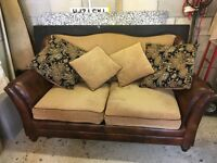 Large two seater leather sofa with material cushion. Dark brown in good condition 200 pound ono