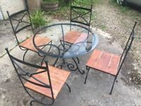 Glass topped, round, wrought iron dining table and four chairs