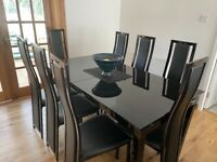 Extendable glass topped dining table, and 8 matching chairs