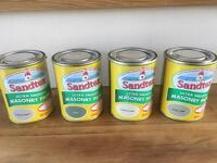 Sandtex Masonry Paint sample pots.