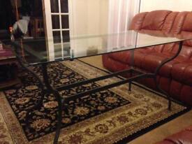 Modern glass table with dark grey metal frame.