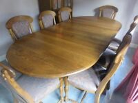 Solid Belgian oak extending dining table and 8 chairs with matching tall cabinet.