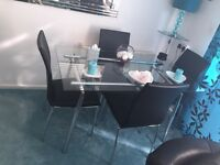 Glass table & 4 black leather chairs.. ( only one chair sat on )