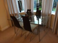 Glass topped chrome dining table with 4 matching fabric and faux leather backed chairs.