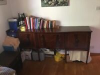 Polished wood sideboard with three central drawers and two side doors with integral shelves.