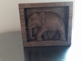 Carved elephant in wooden frame all one piece.