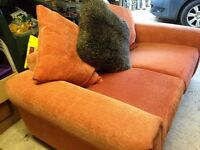 Burnt orange two seater setee with loose back cushions