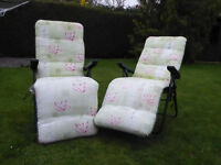 Two reclining garden chairs with padded covers.
