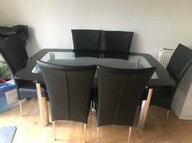 Black and glass rectangular dining table with 6 black chairs