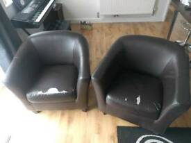 Two brown tub chairs.