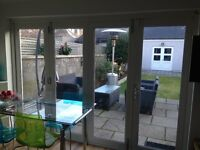 Set of large white bi-folding patio doors and window with timber frame