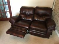 Two seat oxblood leather recining sofa, two reclining chairs and matching stool.