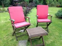 Two garden chairs and small table wood with chair covers . All fold flat for storage.
