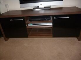 T.V unit dark brown with two black doors.
