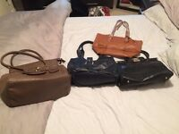Two brown, one black and one navy handbag