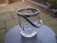 A cut glass ice bucket with silver coloured collar and handle.